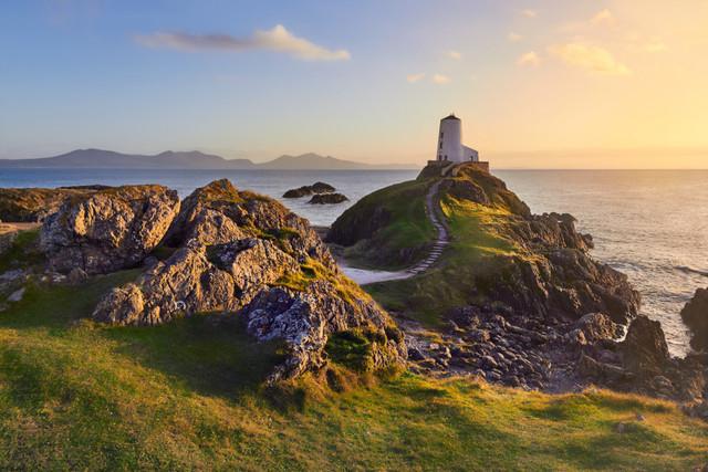 Romantischer Abend am Leuchtturm | Ein Sonnenuntergang an der Küste ist bereits romantisch. Mit einem Leuchtturm auf einem kleinen Hügel und dem Postkartenhimmel darüber kommt einem das Wort