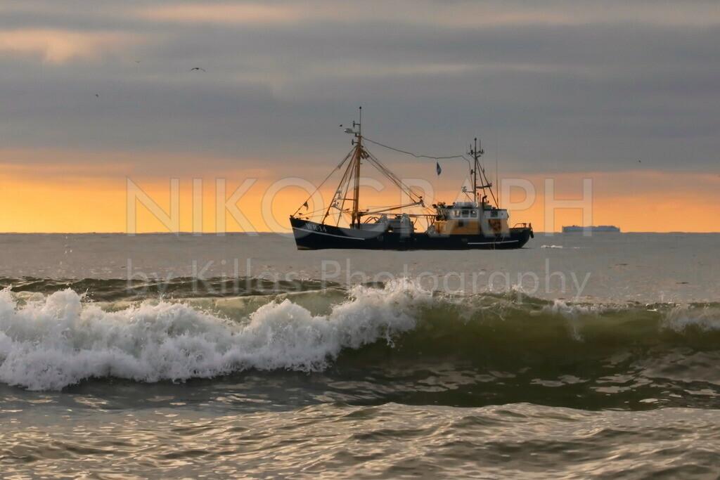 Fischerboot im Abendhimmel | Ein Fischerboot auf der Nordsee vor der malerischen Kulisse des Abendhimmels. Im Vordergrund bricht eine Welle am Strand.