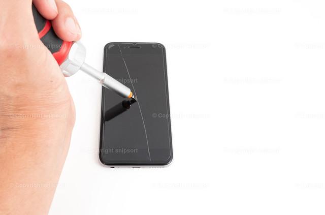 Kratzer auf der Smartphone-Oberfläche | Eine männliche Hand mit einem Schraubenzieher hinterlässt einen dicken Kratzer auf der Handyoberfläche.