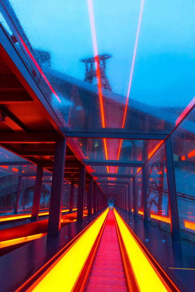 JT-180312-087 | Welterbe Zeche Zollverein, Fördergerüst Schacht 12, Essen, gesehen durch die Regennasse Glasscheibe der Rolltreppe zum Ruhrmuseum, Lichtreflexe der rot beleuchteten Fahrtreppe,