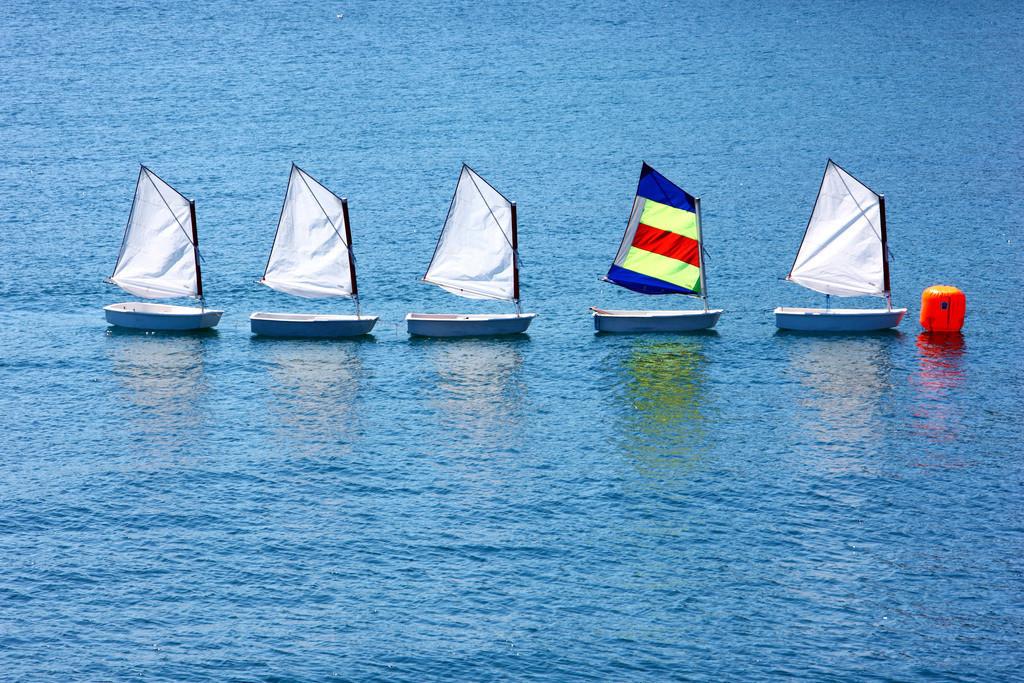 Segelboot | Kleine Segelboote der Optimisten-Klasse, an einer Boje. Gehoeren zu einer Segelschule. Segelunterricht fuer Kinder.