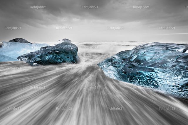 Eisblöcke in der Brandung | Goße Eisblöcken an einem schwarzen Strand mit starker Brandung, die Wasserbewegung ist zu sehen (Langzeitbelichtung, deutliche Bewegungsspuren), darüber ein kontrastreicher grau bewölkter Himmel, Tiefenwirkung durch Perspektive, Bearbeitung im Stil