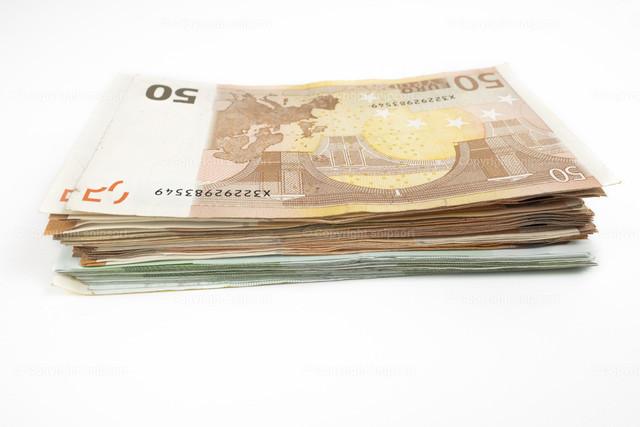 Geldstapel | Ein Geldstapel mit mehreren Fünfziger und Hundertern auf weißem Hintergrund.