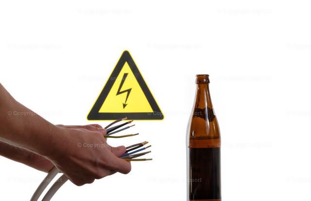 Gefahr von Alkohol am Arbeitsplatz  | Konzept der Gefährlichkeit von Alkohol am Arbeitsplatz beim Hantieren mit Strom.