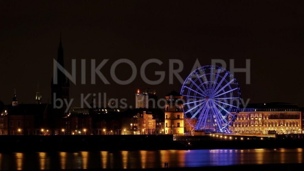 Die Rheinpromenade in Düsseldorf | Die Rheinpromenade in Düsseldorf bei Nacht. Das Riesenrad, neben dem markanten Schlossturm, ragt mit seinen 42 Gondeln im Nachthimmel empor. Die Lichter der Düsseldorfer Nacht spiegeln sich im Rhein.