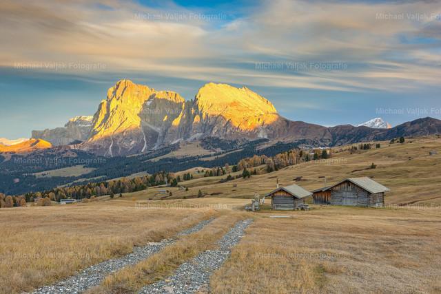 Herbst auf der Seiser Alm | Die letzten Sonnenstrahlen des Herbsttages treffen auf den Lang- und Plattkofel und tauchen die Felsen in ein warmes Licht.