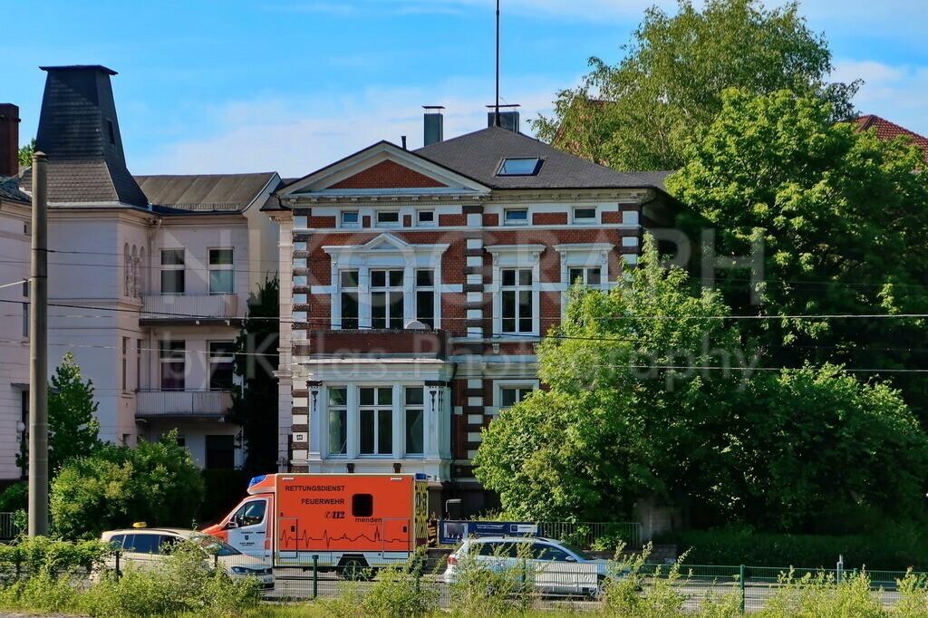 Iserlohner Strassensicht   Ein Rettungswagen aus Menden vor einem Iserlohner Stadthaus.
