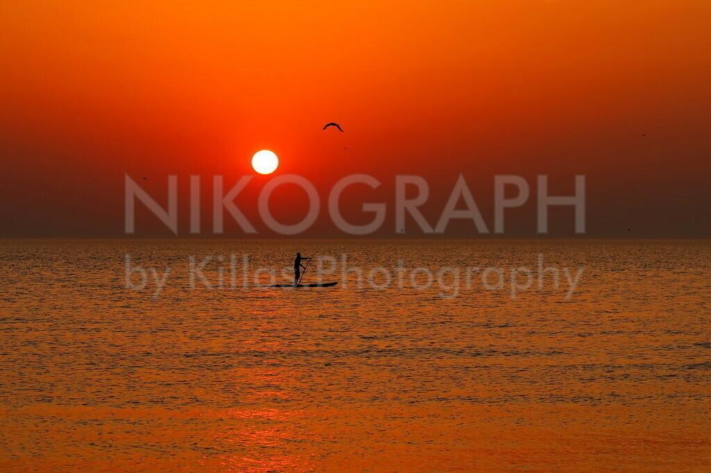 Sonnenuntergang am Strand | Ein Sonnenuntergang am Strand von Texel. Das Abendrot der Sonne spiegelt sich im Wasser der Nordsee und der Himmel verfärbt sich Glutrot. Ein Stand-Up-Paddler paddelt über die Nordsee.
