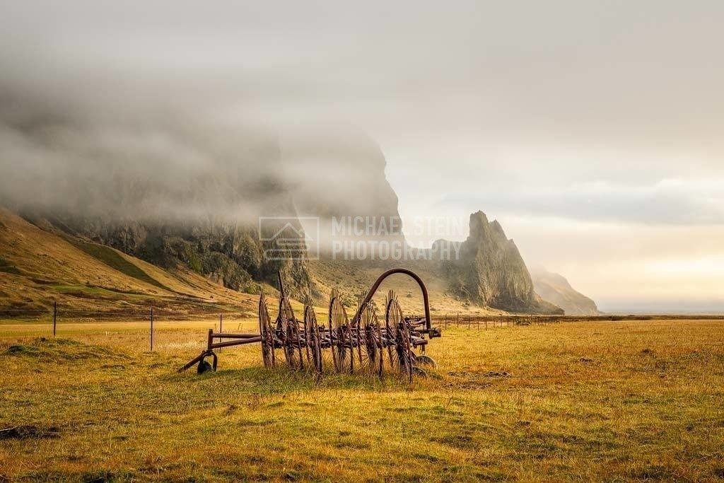 Island - Berge im Nebel   Alter Pflug auf goldenem Gras bei Vik mit Nebel