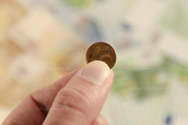 1 Cent in der Hand vor Geldscheinen im Hintergrund | Detail von einer Hand mit einem Centstück vor vielen Geldscheinen im Hintergrund.