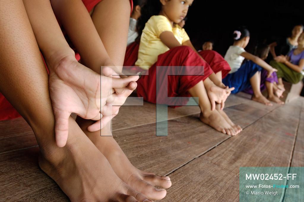 MW02452-FF | Kambodscha | Phnom Penh | Reportage: Apsara-Tanz | Für die Schülerinnen der Tanzschule beginnt jede Tanzstunde mit Aufwärmübungen. Sechs Jahre dauert es mindestens, bis der klassische Apsara-Tanz perfekt beherrscht wird. Kambodschas wichtigstes Kulturgut ist der Apsara-Tanz. Im 12. Jahrhundert gerieten schon die Gottkönige beim Tanz der Himmelsnymphen ins Schwärmen. In zahlreichen Steinreliefs wurden die Apsara-Tänzerinnen in der Tempelanlage Angkor Wat verewigt.   ** Feindaten bitte anfragen bei Mario Weigt Photography, info@asia-stories.com **