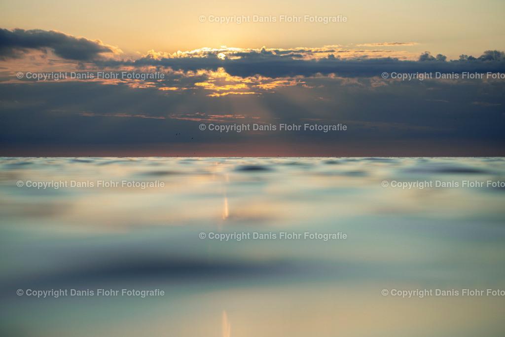 Strahlen | Sonnenstrahlen durchbrechen die Wolken, das Meer spiegelt die Wolken und die Sonne