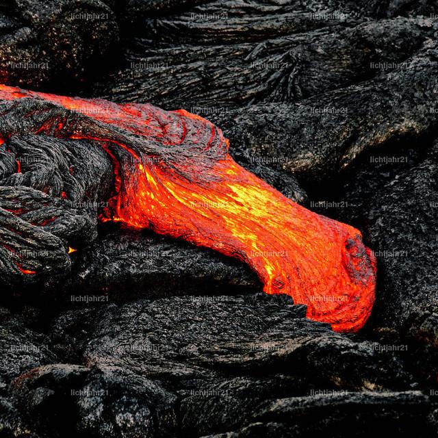 Glühende Lava tritt aus einer Erdspalte aus | Heißes Magma tritt aus einer Erdspalte aus als Teil eines aktiven Lavastroms, die glühende Lava kühlt langsam ab und erstarrt - Location: Hawaii, Big Island, Vulkan