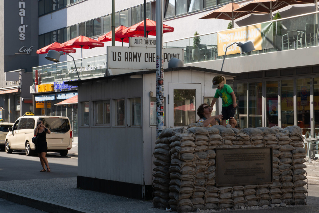 rebellion | Touristic Scene on Checkpoint Charlie in September 2020. A child with a green t-shirt goes up the barricades and covers her mother's mouth.