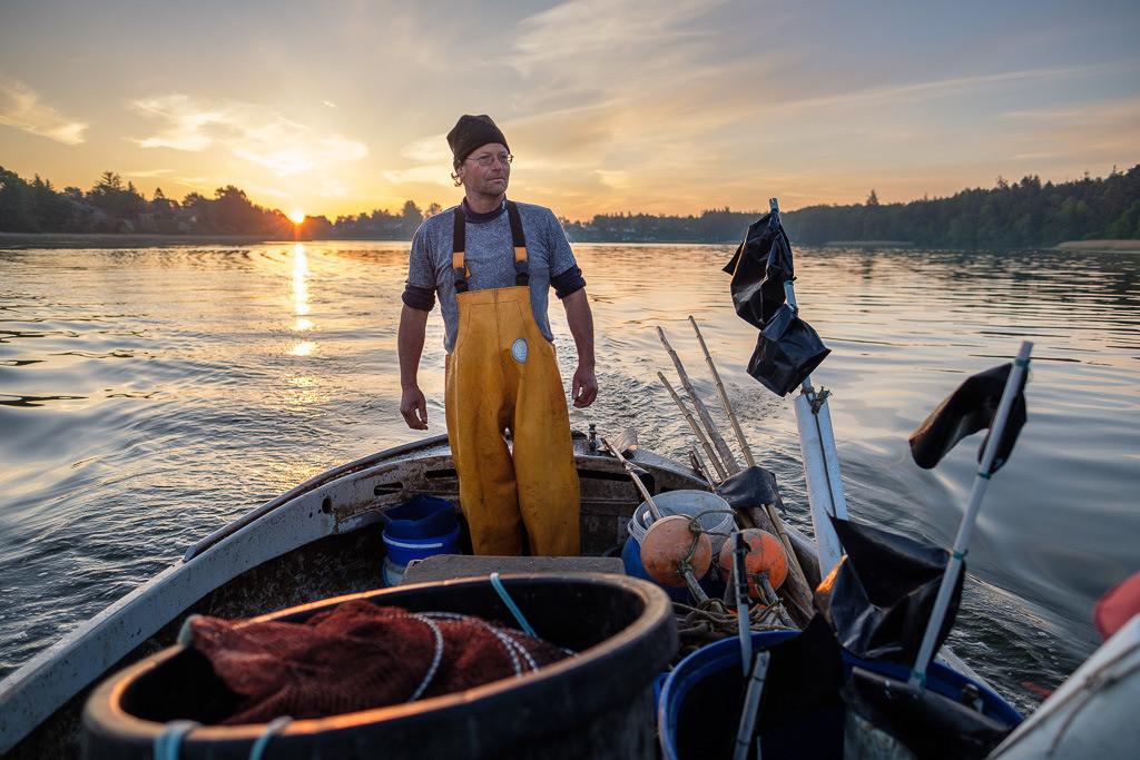 Matthias Nanz – ein Fischer an der Schlei © Holger Rüdel | Matthias Nanz bei Sonnenaufgang im Mai auf der Fahrt zu seinen Reusen in der Großen Breite der Schlei. Matthias Nanz ist einer der letzten Berufsfischer an der Schlei. Die Fischerei war früher prägend für den Schleswiger Stadtteil Holm, in dem Matthias Nanz lebt.