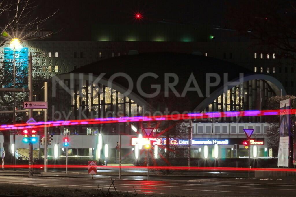 Opernhaus Dortmund   Das Opernhaus in Dortmund bei Nacht. Die vorbeifahrenden Fahrzeuge ziehen am Südwall ihre Lichtspuren. Das blinkende Blaulicht eines Rettungswagens zieht eine gestrichelte Linie durch das Bild.