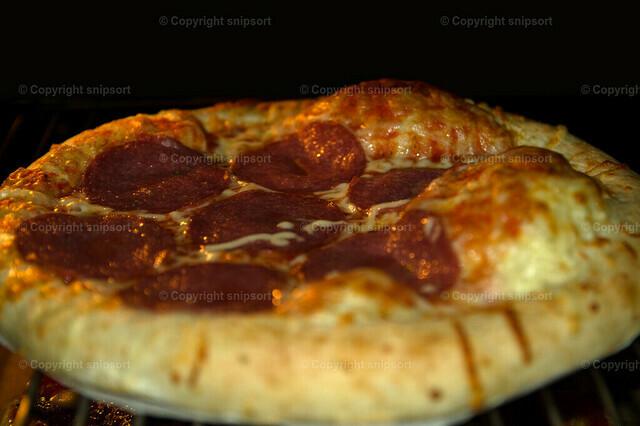 Pizza auf dem Backblech | Eine Pizza im Ofen auf einem Gitterrost.