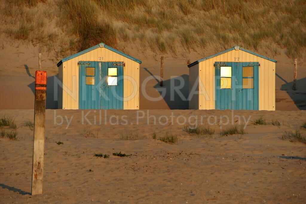 Strandhütten auf Texel | Das Abendlicht der untergehenden Sonne spiegelt sich in den Strandhütten am Strand. Die Strandhütten sind an fast jedem Strandabschnitt auf Texel zu sehen. Dort können Strandliegen, Sonnenschirme und weitere Strandutensilien gelagert werden. Zur Wintersaison werden die Strandhütten hinter den Deichen in Sicherheit gebracht, um diese vor den Herbst- und Winterstürmen der Nordsee zu schützen.   Im Vordergrund der markante Pal der auf Texel die verschiedenen Strandabschnitte markiert.