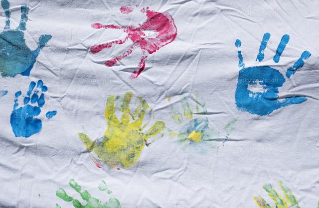 Bunte Handabdrücke | Bunte Abdrücke von Kinderhänden auf einem weißen Laken.
