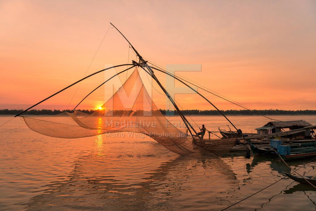 Fischernetz | Sonnenuntergang am Mekong-Fluss. Mit einem riesigen Senknetz holt der Kambodschaner die Fische aus dem Mekong.
