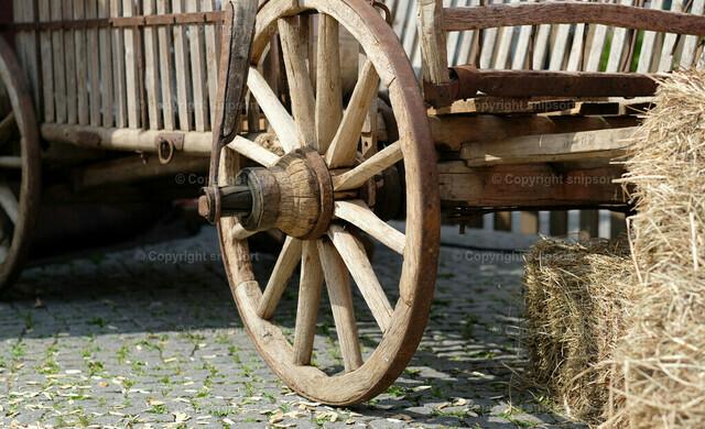 Karren neben Heuhaufen | Detail von einem Karrenrad neben einem Heuhaufen.