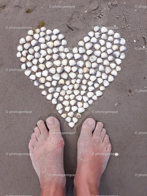 zwei Füße stehen vor einem Muschelherz am Strand | zwei nackte Füße am Strand vor einem Herz aus Muscheln im Sand bei Tageslicht