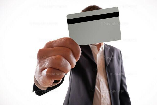 Bankangestellter mit einer Geldkarte mit Magnetstreifen. | Mann mit Anzug streckt einem eine Bankkarte entgegen