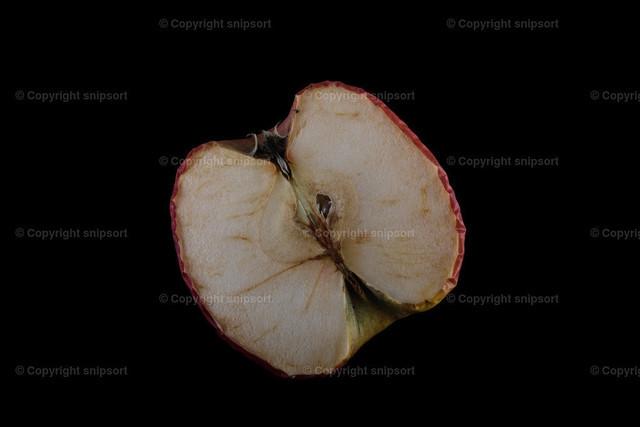Alter, verdorrter Apfel | Eine alte, ausgetrocknete Apfelhälfte vor schwarzem Hintergrund.