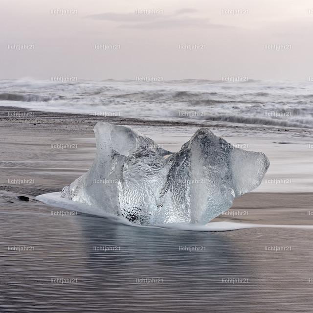 Eisblock am Strand | Markanter Eisblock an einem schwarzen Strand mit Brandung, bei rücklaufenderm Wasser Spiegelung auf dem nassen Sand, im Hintergrund rollen Wellen heran, zarte Rottöne am Himmel und auf dem nassen Sand - Location: Island, Jökulsarlon (Jökulsárlón)
