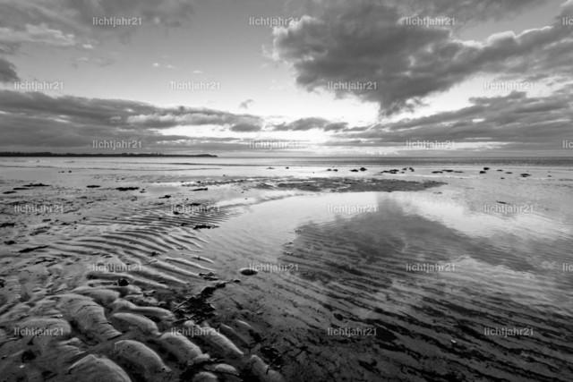 Küstenlandschaft mit Sandrippen und farbigen Wolken | Weiter Blick über eine Küstenlandschaft, kontrastreiches Schwarzweißbild, im Vordergrund Sandrippen, darüber einige farbige Wolken, die sich im flachen Wasser spiegelt - Location: Ostseeküste Insel Rügen, Deutschland