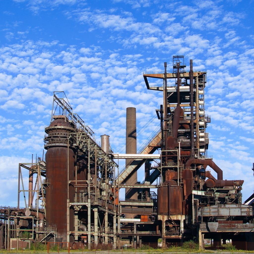 Stillgelegte Industrieanlage in Dortmund   Verrostete und stillgelegte Industrie Barracke im Ruhrpott vor blauem Himmel mit Wolken im Sommer