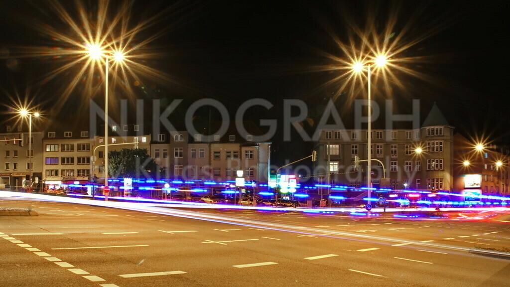 Lichter der Stadt in Hagen   Die Kreuzung am Emilienplatz in Hagen bei Nacht. Ein Rettungswagen fährt mit Blaulicht über die Kreuzung. Das blaue Blinklicht hinterlässt eine pulsierende Spur an der Kreuzung.