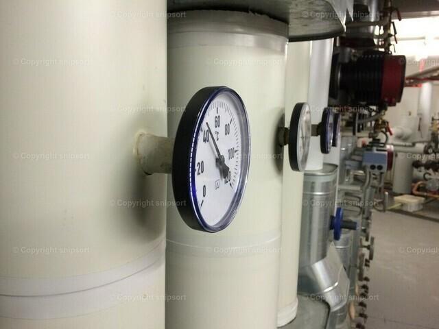 Technikraum | Blick in einen Technikraum an von einem Heizungsverteiler ausgehenden Heizungsrohren.