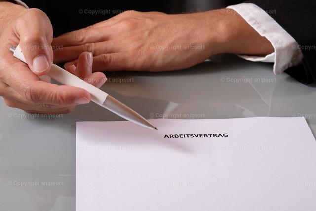 Arbeitsvertrag  | Der Chef reicht dem Bewerber einen Arbeitsvertrag über den Tisch.
