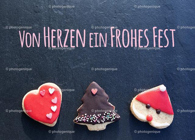 Weihnachtskarte von Herzen ein Frohes Fest | Weihnachtskarte mit drei Weihnachtsplätzchen vor einem dunklen Hintergrund bei Tageslicht mit dem Text von Herzen ein Frohes Fest