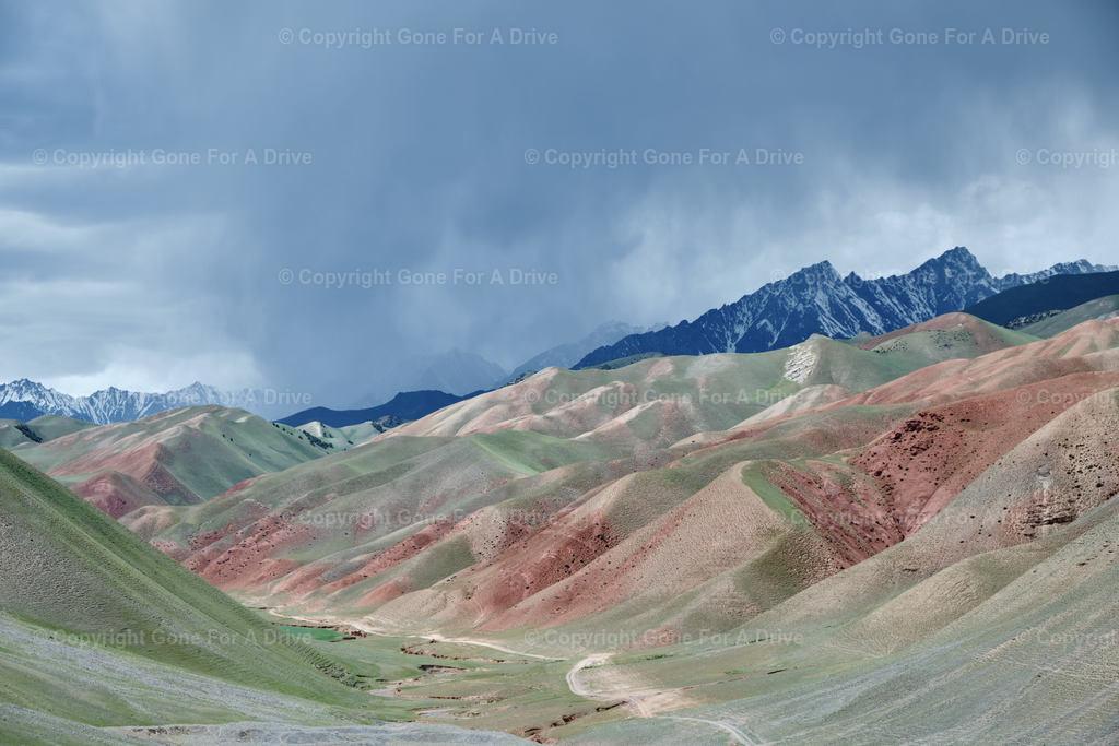 Kirgistan   Grüne Hügel vor schroffen Bergen
