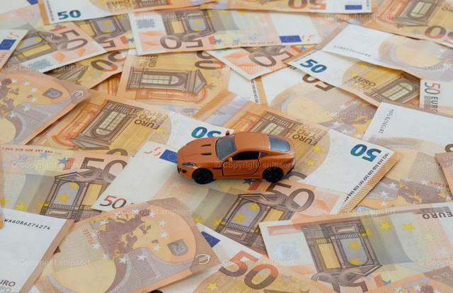 Orangenfarbenes Auto auf einem Geldteppich | Ein Modellauto auf flächendeckend ausgelegten 50-Euro-Banknoten zum Thema Konzept Autokosten