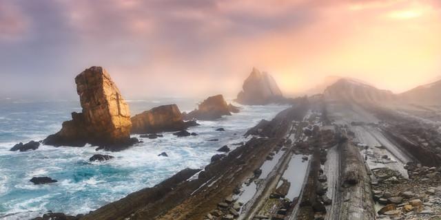 Magie des Lichts | Farbkontraste sind ein wichtiges Stilmittel in der Malerei. In der Fotografie sorgt die Natur manchmal ganz von selbst dafür. Zum Sonnenaufgang, wenn die kühle Luft von den ersten warmen Strahlen getroffen wird und diese auf Felsen und Meer fallen, ist die Chance auf Lichtspektakel am größten.
