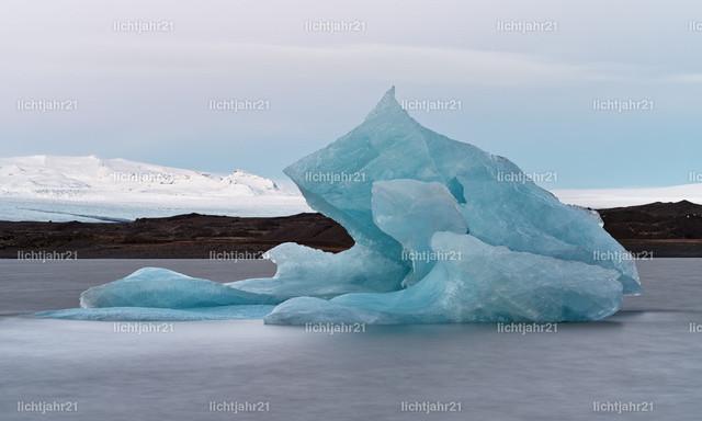 Großer blauer Eisberg vor einem Gletscher | Gletscherlagune mit einem großen blauen Eisberg im Vordergrund, im Hintergrund Berge und ein gewaltiger Gletscher, Licht zum Tagesende, Wasserbewegung geglättet durch Langzeitbelichtung - Location: Island, Südküste