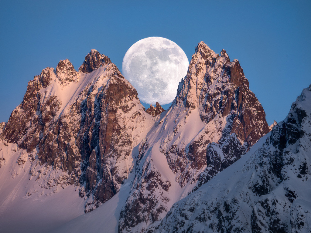 Rise And Fall | The full moon framed between swiss alps mountain peaks.