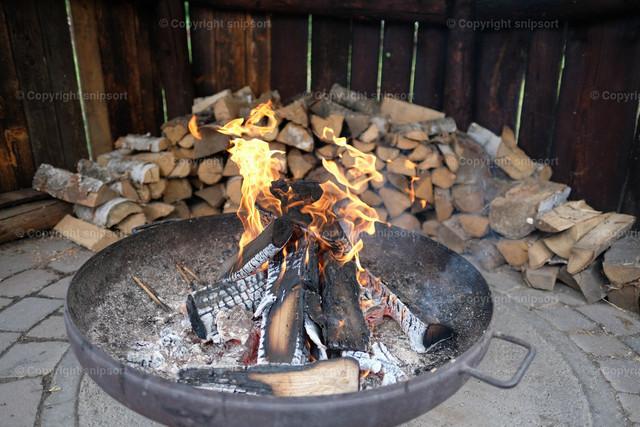 Feuerstelle | Eine Feuerstelle mit Holzscheiten im Hintergrund.