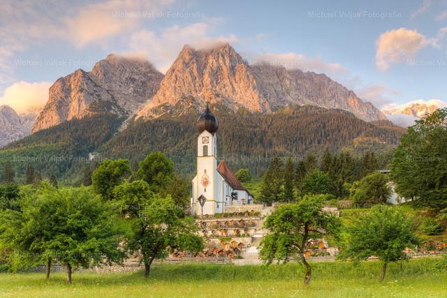 Alpenglühen in Grainau   Frühmorgens bei der Pfarrkirche St. Johannes der Täufer in Obergrainau, als die ersten Sonnenstrahlen des Tages die Berge zum Leuchten bringen.
