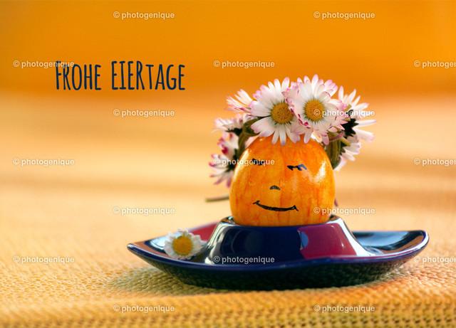 Osterkarte gelbes Osterei: Frohe Eiertage | Osterkarte gelbes Ei mit Gesicht trägt Kranz aus Gänseblümchen bei Tageslicht vor einem gelben Hintergrund mit dem Text Frohe Eiertage