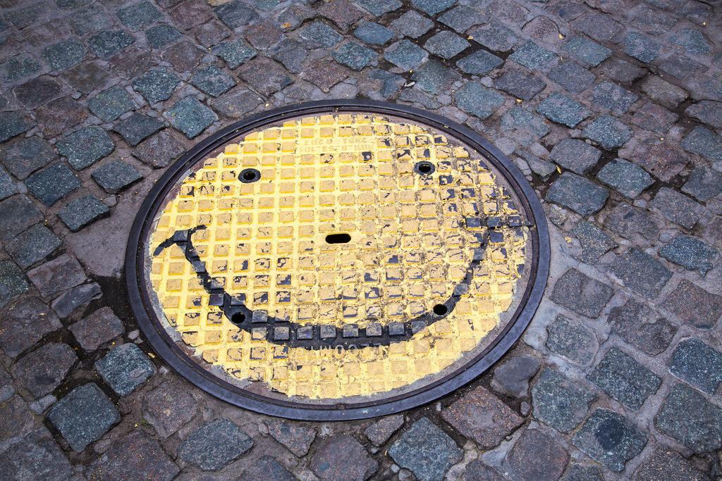JT-140629-064 | Kanaldeckel mit einem Smily Gesicht bemalt,