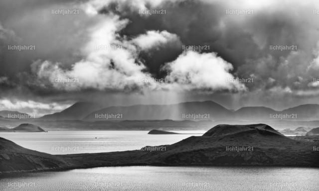 Island - Sonne und Regen am See Myvatn | Schwarzweißaufnahme eines großen Sees mit Inseln, eingerahmt von Bergen, einzelne Bereiche sind von der Sonne beleuchtet, im Hintergrund graue Wolken und Regenschleier - Location: Island, See 'Myvatn'