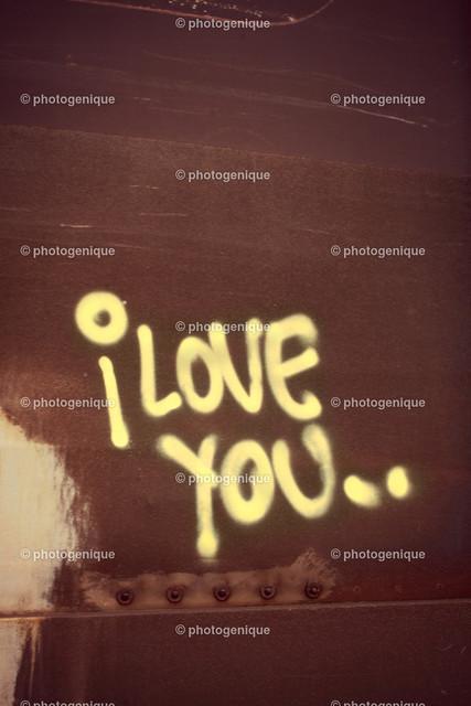 Grafitti I love you | gelbes Grafitti I love you auf rostigem Untergrund bei Tageslicht