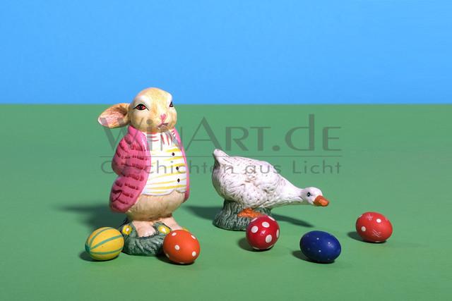 Ein fetter Osterhase und eine Gans zwischen bunten Eiern | Ein dicker Osterhase im Frack und eine Gans stehen zwischen bunten Ostereiern auf einer Wiese.