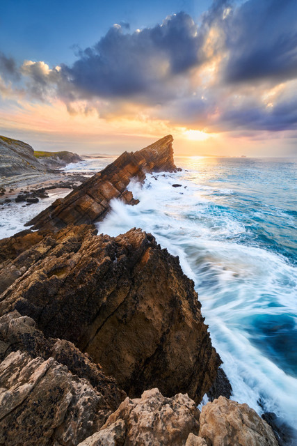 Felsnadel im Meer | Nordspanien ist gespickt mit wilder Küste, fantastischen Felsformationen und allen Elementen, die der Planet Erde bietet. Wenn zum Sonenuntergang das Licht ein letztes mal durch die Wolken bricht und die Felsen zum Leuchten bringt, schlägt das Fotografenherz höher.