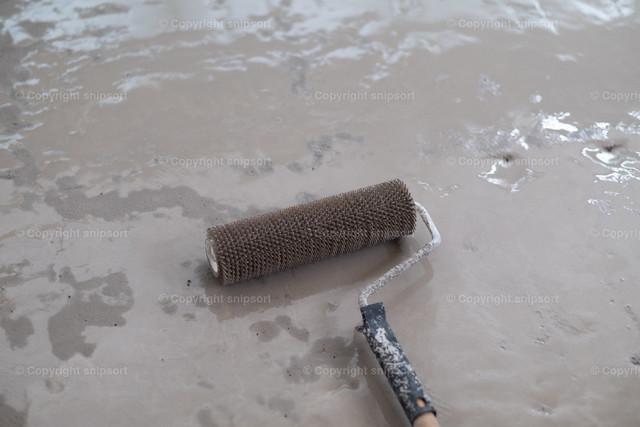 Stachelwalze über flüssiger Bodenausgleichsmasse