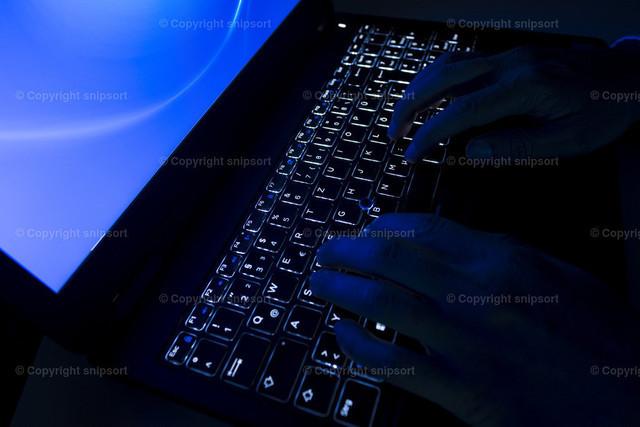 Die Hände eines Hackers auf der Tastatur | Konzept eines Hackers im Dunkeln auf Tastatur mit Hintergrundbeleuchtung tippend.